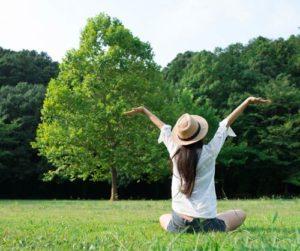 Frau sitzt im Grünen, streckt sich und atmet durch