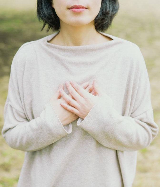 Frau hält Hände vor Ihre Brust
